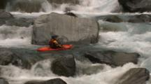 A Pullout From A Kayaker To A Wide Shot Of A Boulder Covered River.