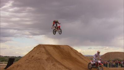 A Line Of Motocross Riders Do Big Tricks.