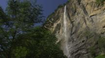Waterfall On Cliff Wall With Trees In The Foreground.