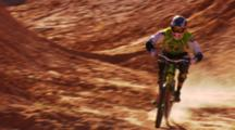 Wide Of A Mountain Biker Going Through A Section Of Small Jumps.