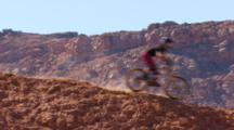 Wide Shot Of A Female Mountain Biker Riding A Ridge Run.