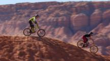 Zoom Out Tracking Of Two Mountain Bikers Riding A Steep Trail.