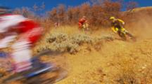 Wide Shot Of A Train Of Mountain Bikers Riding Fast Downhill On A Single Track.
