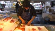 Man Scraping Fish At A Fish Market.