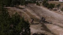 Group Of Mountain Bikers Riding Slowly On A Single Track Through Fields.