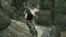 Tracking Two Mountain Bikers Riding A Single Track Through A Boulder Field.