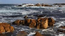 Incoming Waves Crash Along The Rocky Shore Of Pacific Grove, California.