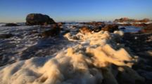 Sea Foam Accumulates On A Beach After Large Winter Waves Break In Pacific Grove, California.