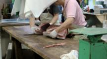 Man Cutting Fresh Tuna With Big Knife At Tsukiji Market In Japan