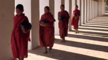 A Line Of Monks Walking With Black Bowls