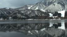 Snowy Mountains Reflect In Glassy Lake