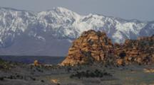 Red Rock Layered Ridge Against Snow Capped Mountains, Sagebrush Flat In Front.
