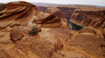 Looking Across Sandstone Rock Formations To Horseshoe Bend, Arizona, Mesa And Colorado River.