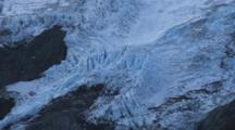 Shot Pans Up Slope. Blue Glacial Ice Covers The Steep Mountains Of The Southern Alps, New Zealand.