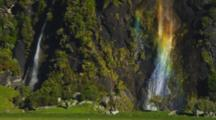 Wave Pattern In Rainbow. Waterfall With Multi-Colored Rainbow Streams Down Rocky Cliff With Thick Vegetation. Second Waterfall To The Left.