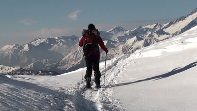 Woman trekking on a snow field,mountains ahead