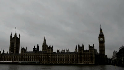 time lapse clouds move above silhouetted dPalace Of Westminster,London,boats on river