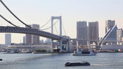 Boats cruising at Tokyo Bay and Tokyo cityscape with Rainbow Bridge in the background,Tokyo,Japan