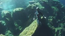 A Female Free Diver Sits Motionless On A Rock At The Entrance Of A Cenote