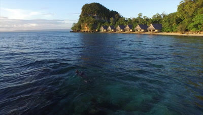 Snorkeler on house reef at remote resort in Raja Ampat