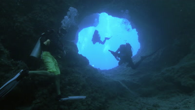 group of scuba divers leave under water cave,Palau