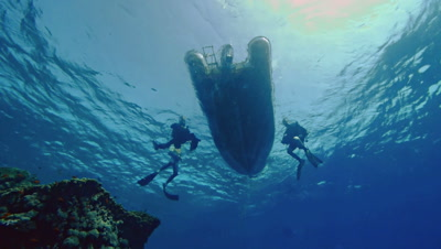 wide shot of scuba divers picked up by inflatable dinghy,under water point of view,water surface,small waves,clear water,tropic waters,Red Sea