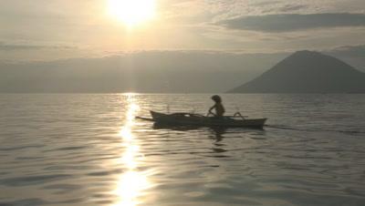 Small Indonesian Prahu Boat Near Bunaken Island At Sunset