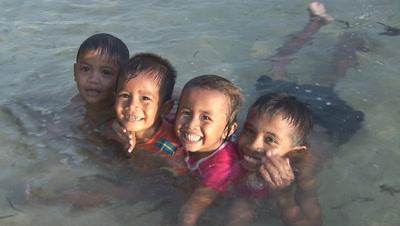 Smiling Indonesian Children In Shallow Water At Bunaken Island