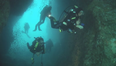 Divers Swim Through Underwater Arch