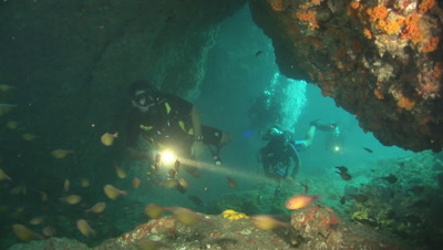 Scuba Divers With Flashlights Explore Underwater Cave