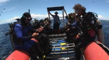 Scuba Divers Roll Backwards Off Small Boat Into The Water