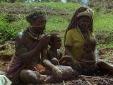 Mendi Family Sit By Fire, Father Passes Food To Baby To Eat.