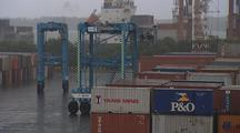 Mws Container Port, Pan Blue Empty Straddle Crane Travels Between Containers Towards Cam Then Turns R, Second Blue Crane Moving Behind.