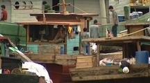 Busy Men On Small Wooden Cargo Boats Crammed In Port.