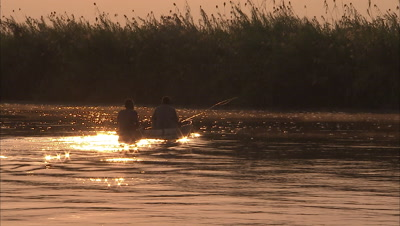 Two Fisherman in mokoro at sunrise on river