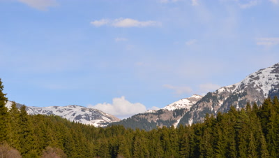 Time Lapse,Clouds Moving Over Snow Capped Mountains,Coniferous Forest