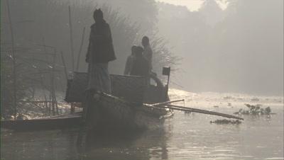 Traditional Fishermen In Boat on Misty River
