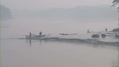 Fishermen Adjusting Fishing Nets In River