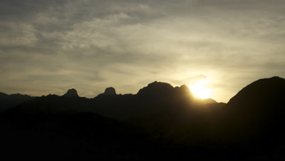 Time Lapse of sun rising over mountains and cloudy skies at Komodo National Park