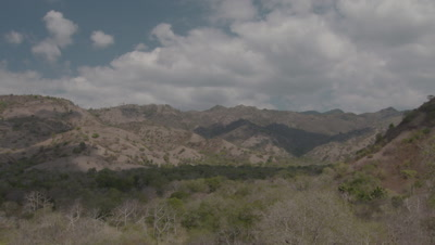 Cloud timelapse over dry hilly forest landscape