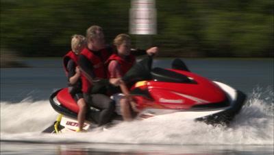 Family Rides Jet Ski Near Pelicans