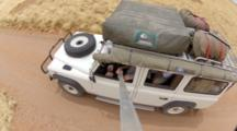 View From Pole Cam Above, Off Road Safari Vehicle Drives Through Desert
