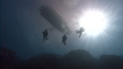 Three divers descend from a boat,all silhouetted