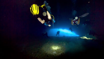Divers swim through underwater cavern