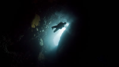 SCUBA DIver descends into and exits underwater cavern
