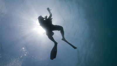 Scuba Diver silhouetted against the sun