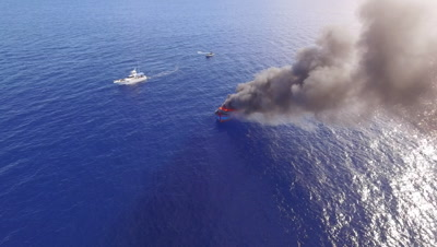 Aerial drone shot descending towards burning illegal fishing boat