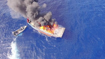 aerial drone shot of burning illegal fishing boat and Police tenders