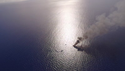 High altitude wide shot of burning illegal fishing boat