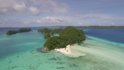 Aerial shot reveals tropical beach with tourist boats in Palau